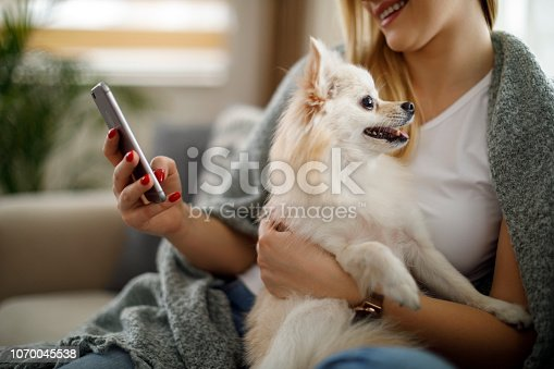 483426960istockphoto Young woman using mobile phone at home 1070045538