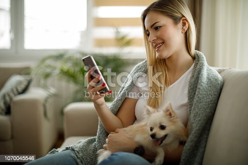 483426960istockphoto Young woman using mobile phone at home 1070045546
