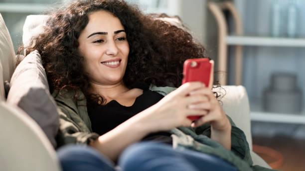 Junge Frau mit Handy zu Hause – Foto