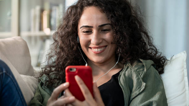 Young woman using mobile phone at home stock photo