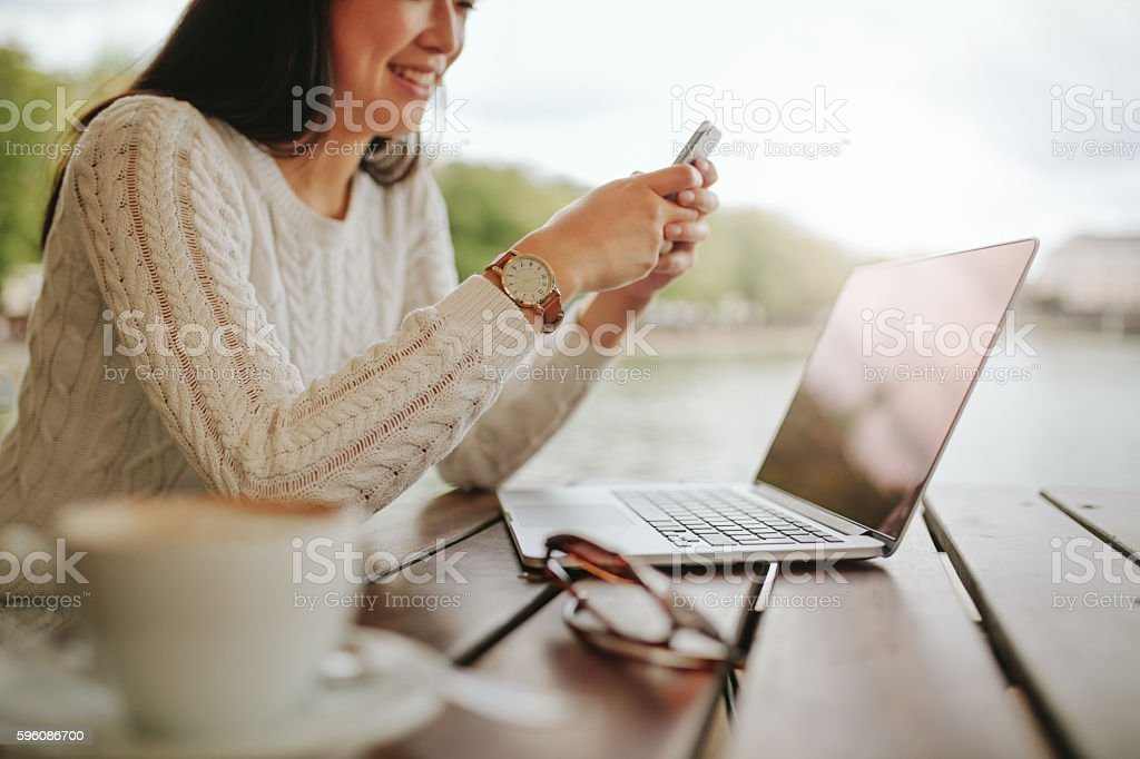 Young woman using mobile phone at outdoor cafe stock photo