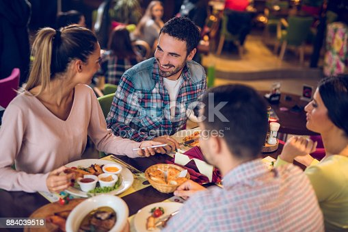 Young woman using mobile phone during lunch with friends in a restaurant.