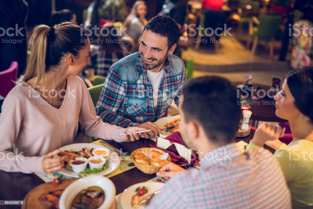 Young woman using mobile phone during lunch with friends stock photo
