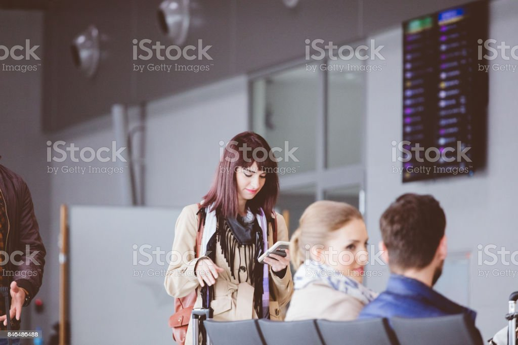 Young woman using mobile phone in airport terminal stock photo