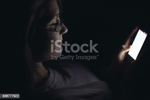 660640502 istock photo Young woman using mobile phone in dark room at night 638777622