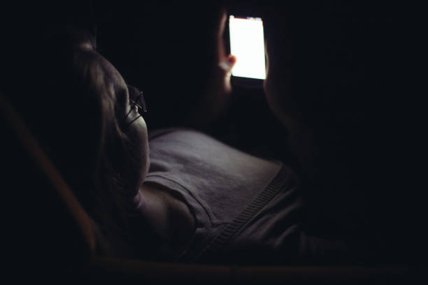 young woman using mobile phone in dark room at night - jugendbett stock-fotos und bilder