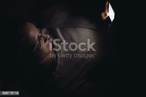 660640502 istock photo Young woman using mobile phone in dark room at night 638778116