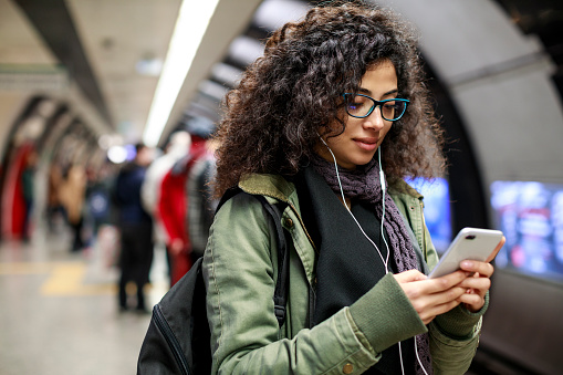 Young woman using mobile phone in the subway station