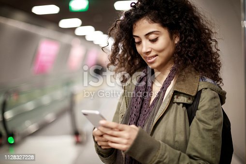 istock Young woman using mobile phone in the subway station 1128327228