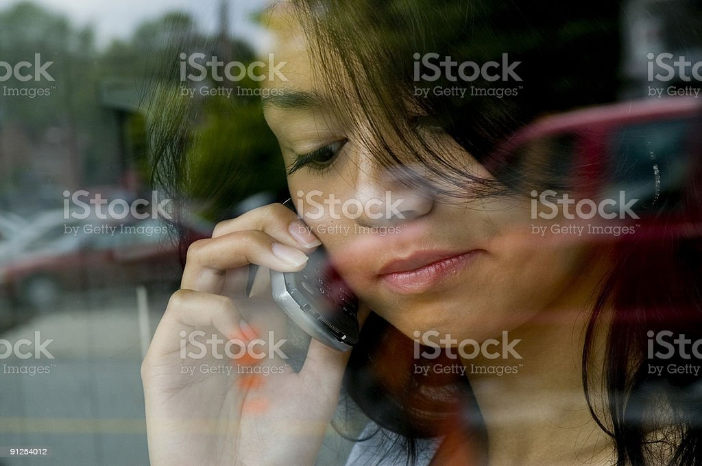 Young woman using mobile phone inside building stock photo