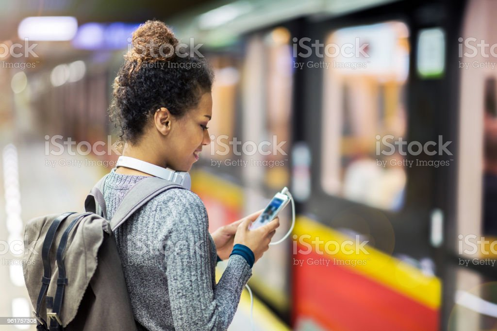 Young woman using mobile phone on subway royalty-free stock photo