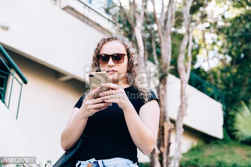 istock Young woman using mobile phone 1161317617