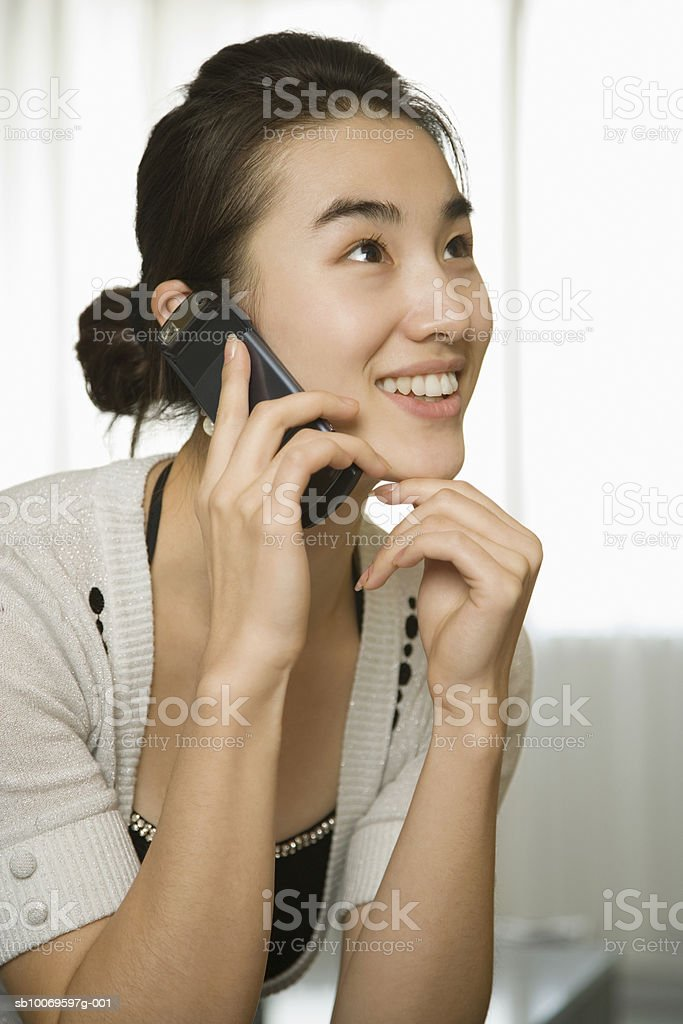 Young woman using mobile phone, smiling foto de stock libre de derechos