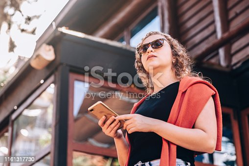 istock Young woman using mobile phone waiting for taxi ride 1161317730