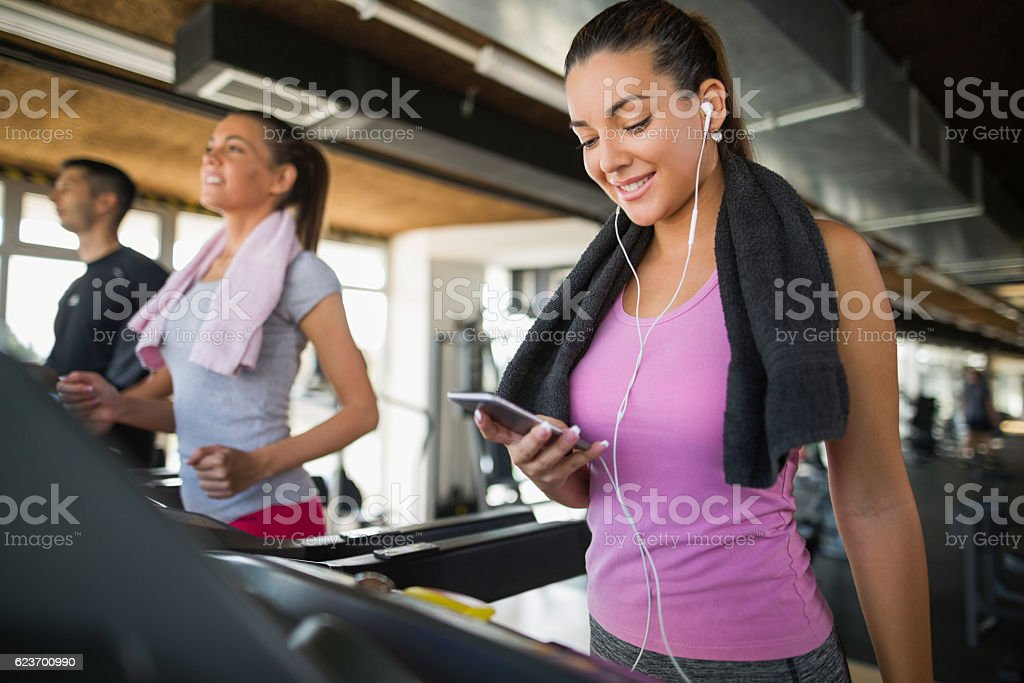 Young woman using mobile phone while exercising on treadmill. stock photo