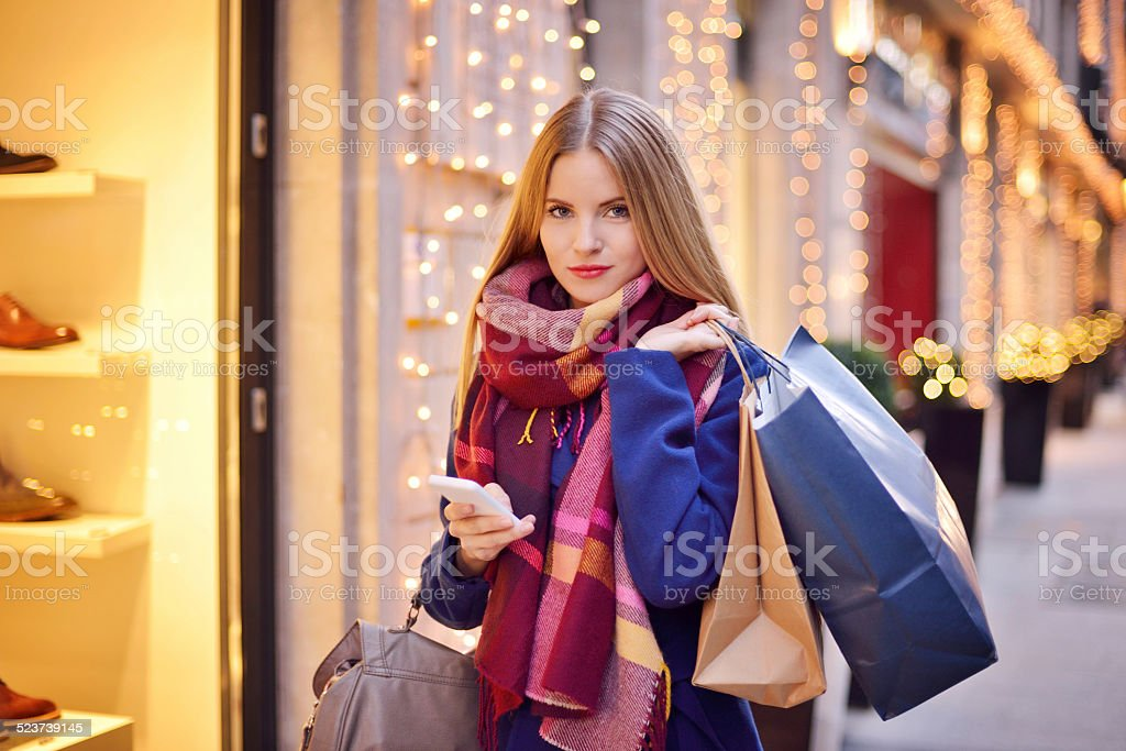 Young woman using mobile phone while shopping stock photo