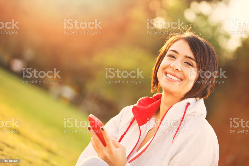 Young woman using mobile telephone outside stock photo