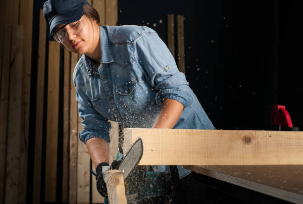 Young woman  using modern electric  saw for ctting wood  in the workshop stock photo