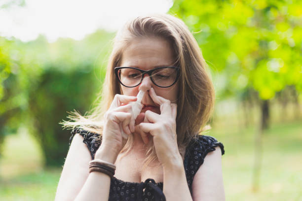 Young woman using nose spray for allergy outdoors stock photo