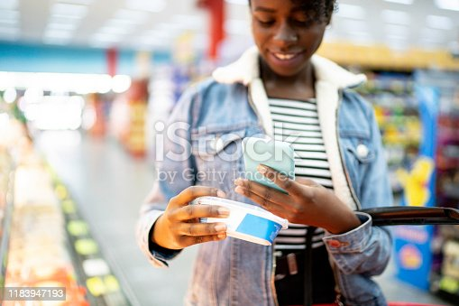 1184048369 istock photo Young woman using phone and choosing products in supermarket 1183947193