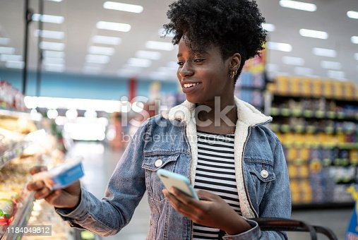 1184048369 istock photo Young woman using phone and choosing products in supermarket 1184049812