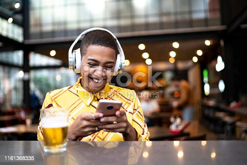 istock Young woman using phone and listen to music at a bar 1161368335