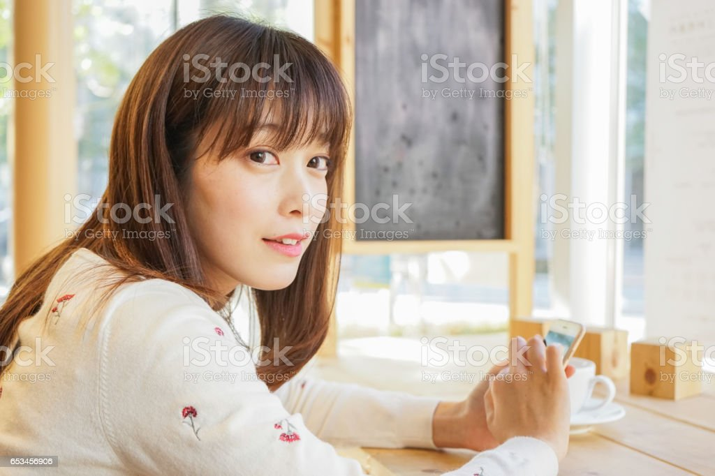 Young woman using phone at cafeteria stock photo