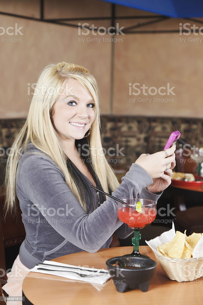Young Woman Using Phone at Restaurant royalty-free stock photo