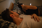istock Young woman using phone in bed while her husband is asleep 1212114534