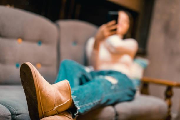 junge frau mit telefon im innenstadt-café - lammfellstiefel stock-fotos und bilder