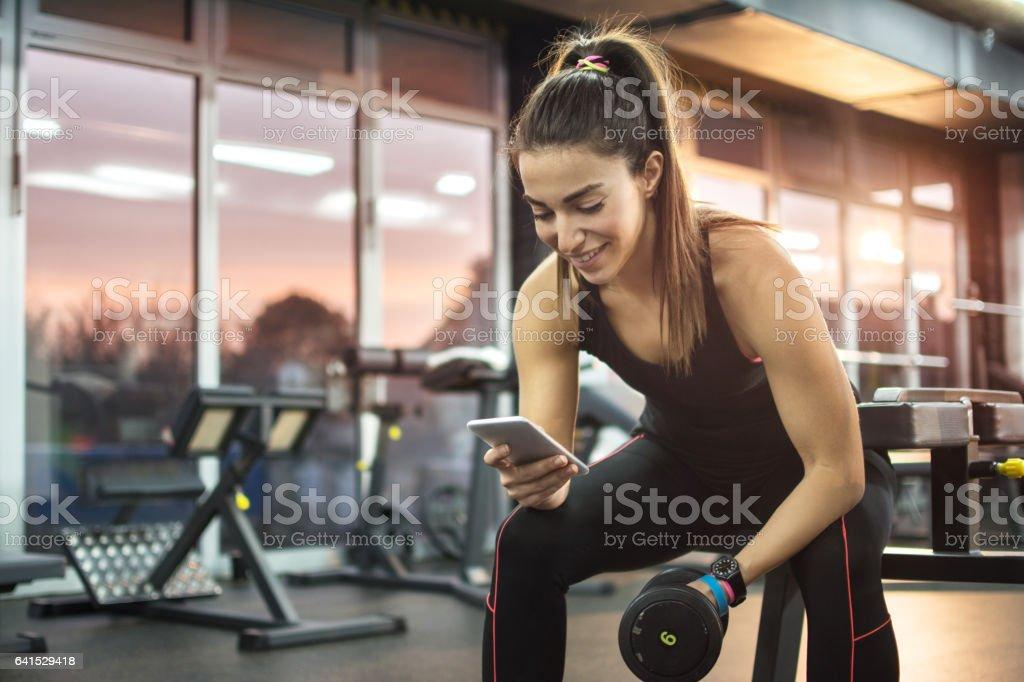 Mujer joven con teléfono en gimnasio. - foto de stock