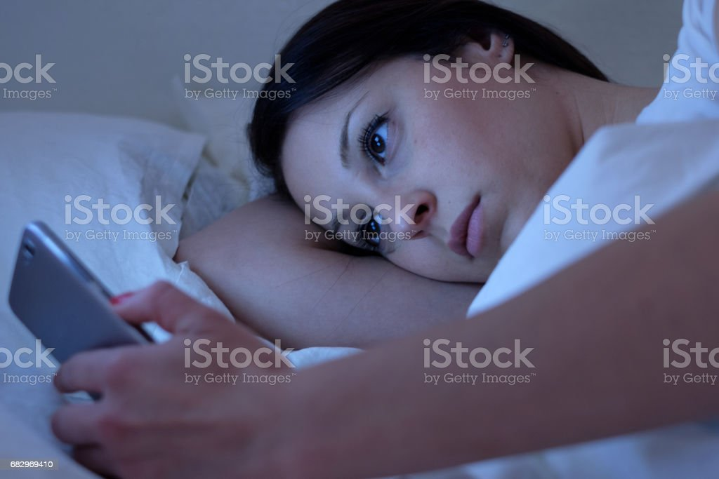 Young woman using phone lying in bed royalty-free stock photo