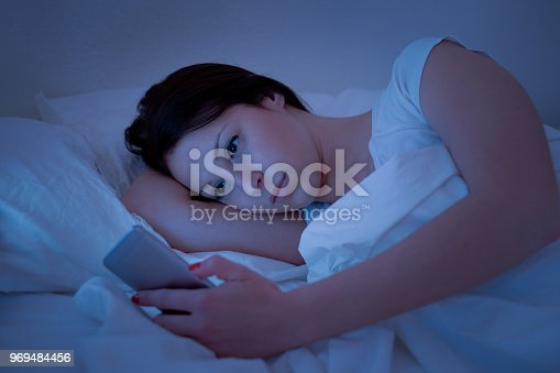 660634310 istock photo Young woman using phone lying in bed 969484456