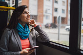 Young elegant woman sitting in a bus and using phone