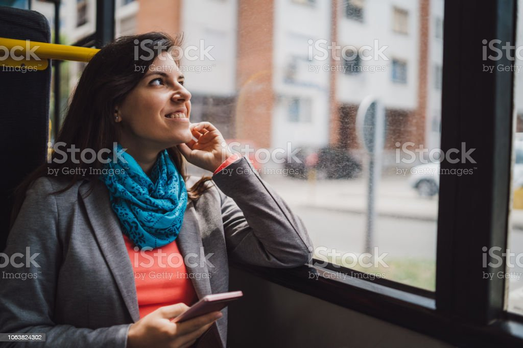 Young woman using phone on a city bus ride stock photo