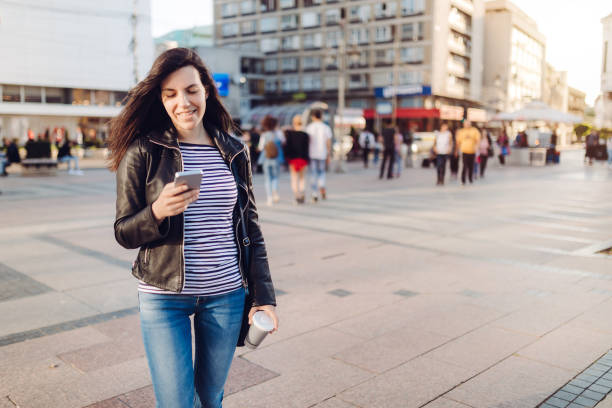 Young woman using phone on a town square stock photo