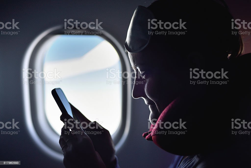 Young woman using phone on the airplane stock photo