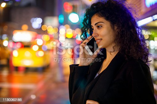 Young woman using phone on the streets of big city at night