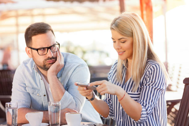 Young woman using phone while sitting at cafe with her boyfriend Internet addiction. Attractive woman messaging online via social networks while sitting at cafe with her boyfriend who is having unhappy and bored look bad date stock pictures, royalty-free photos & images