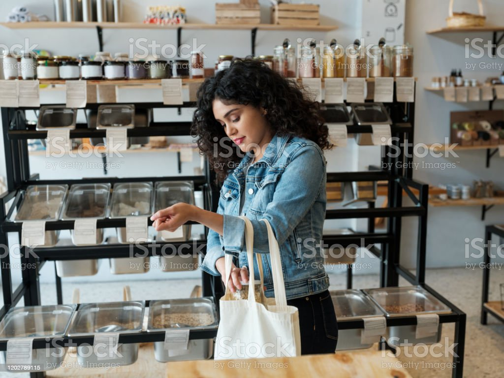 Young woman using reusable shopping bag in store A young latin woman using a reusable shopping bag in a zero waste store. 20-29 Years Stock Photo