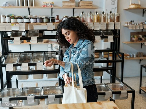A young latin woman using a reusable shopping bag in a zero waste store.