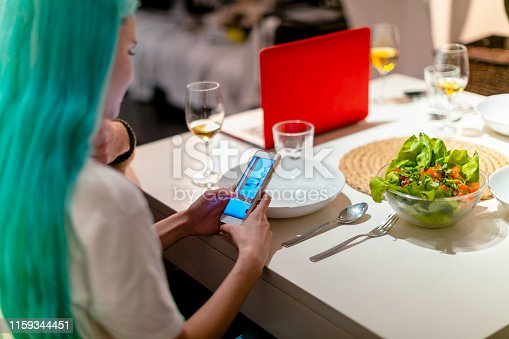 Young woman with turquoise hair using smart phone at dinner table
