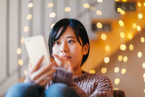 Young Woman Using Smart Phone At Home stock photo