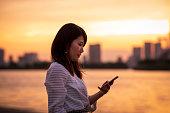 東京ベイエリアでスマートフォンを使う若い女性