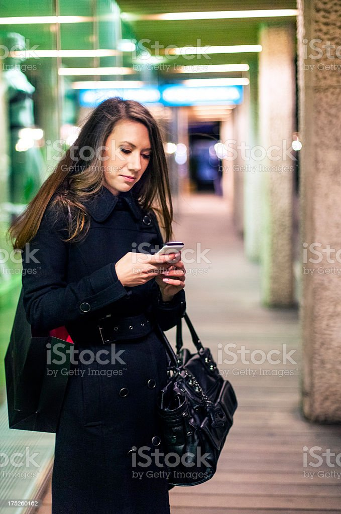 Young woman using smart phone in front of store window royalty-free stock photo