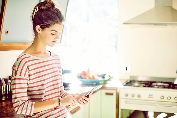 junge frau mit smartphone in der küche - telefonschrank stock-fotos und bilder