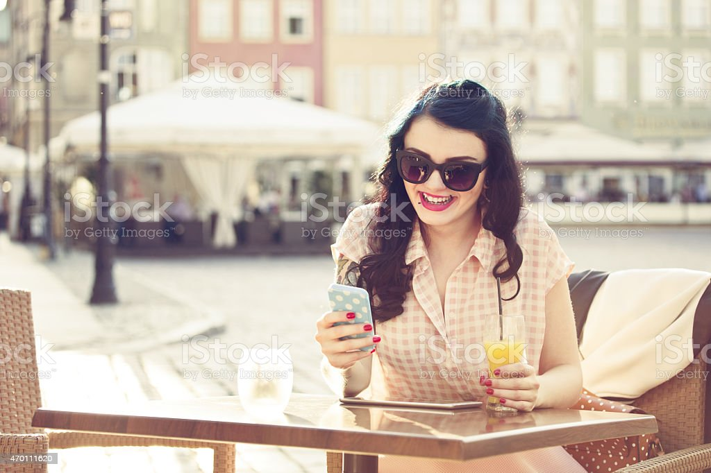Young woman using smart phone in outdoor restaurant Cheerful young woman wearing sunglasses sitting at the table in outdoor restaurant in the city, drinking orange juice and surfing the net using smart phone. Summer time.  2015 Stock Photo