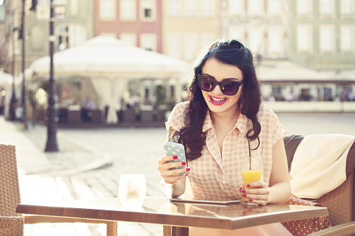 Young Woman Using Smart Phone In Outdoor Restaurant Stock Photo - Download Image Now