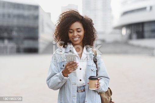 istock Young woman using smart phone on a city street 1301953709