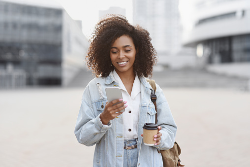 Mixed race student girl using mobile phone on a city street. Freelance work, communication, business, connection, mobile apps, meeting online, travel concept